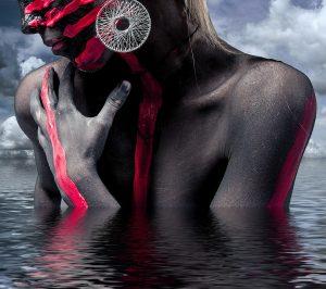 Mensch im Wasser mit roter Farbe bemalt